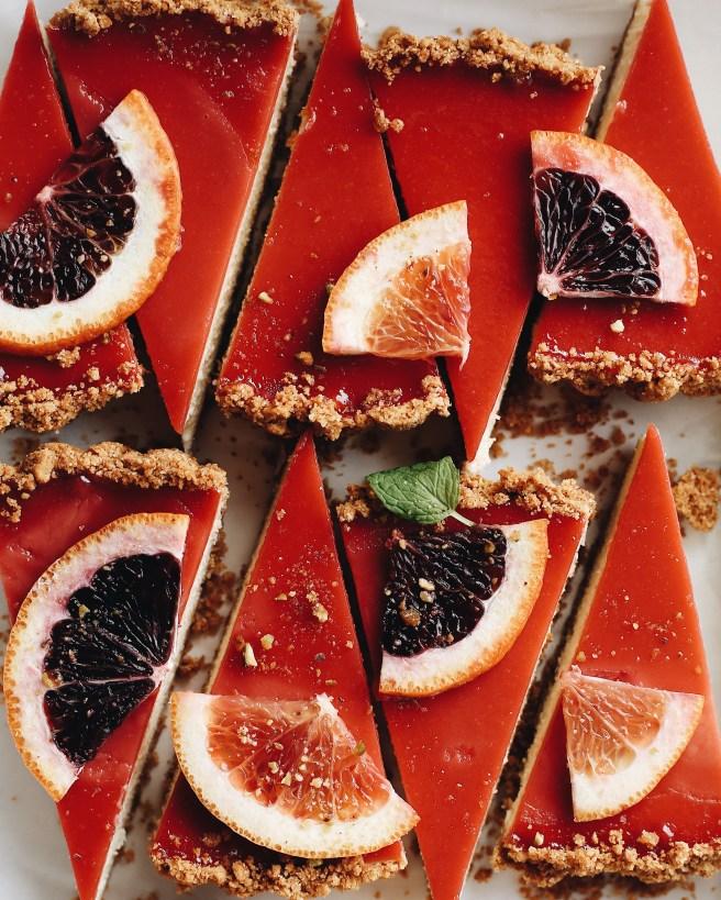 Multiple slices of blood orange cheesecake curd with slices of blood orange on top