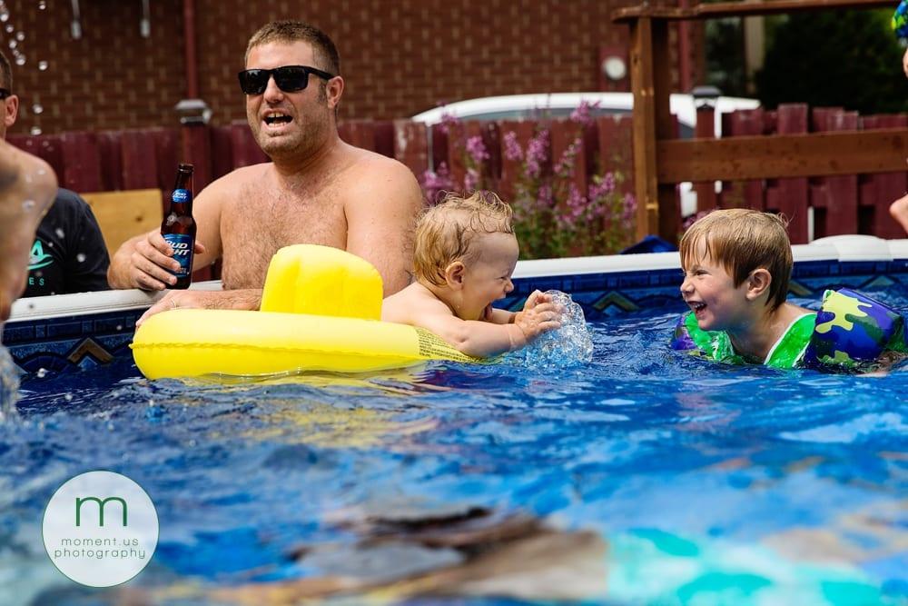 little boy splashing brother in pool