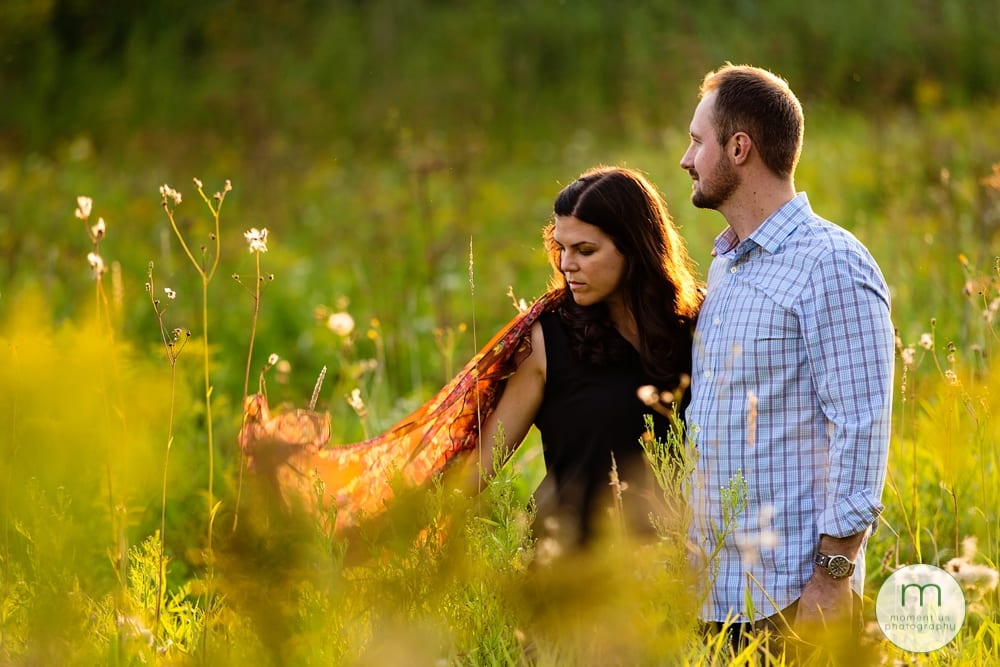 couple standing in tall grass with scarf