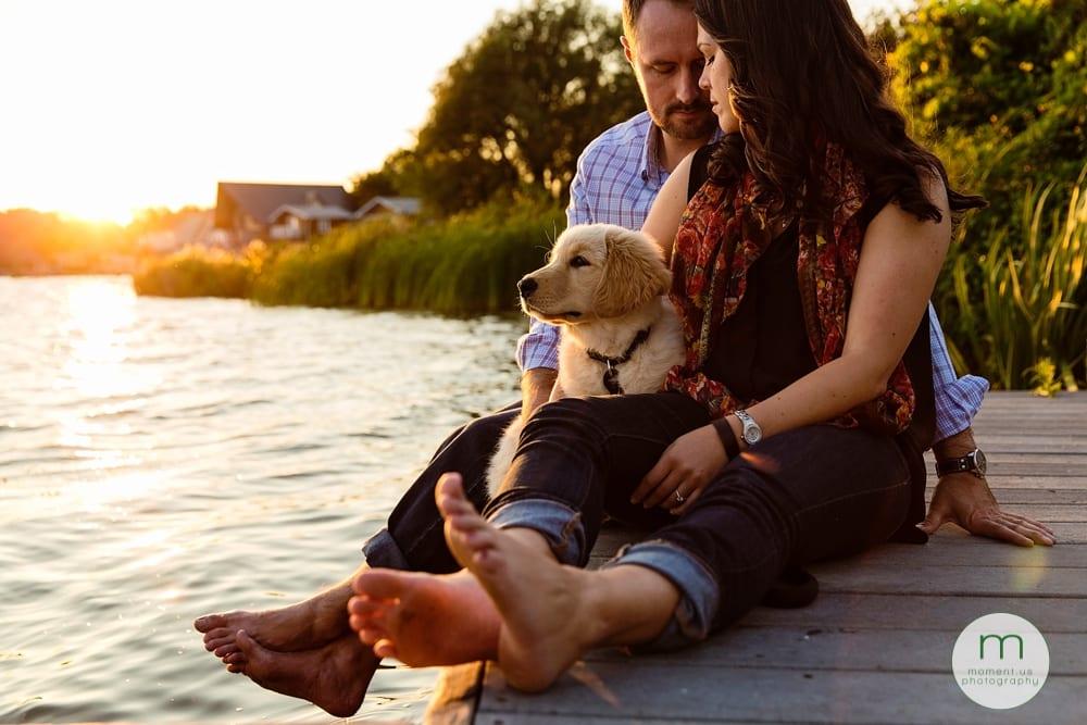Couple cuddling with dog on dock