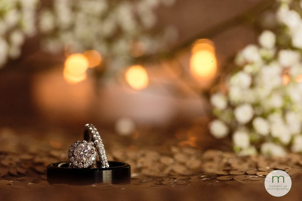 rings in front of candles and baby's breath