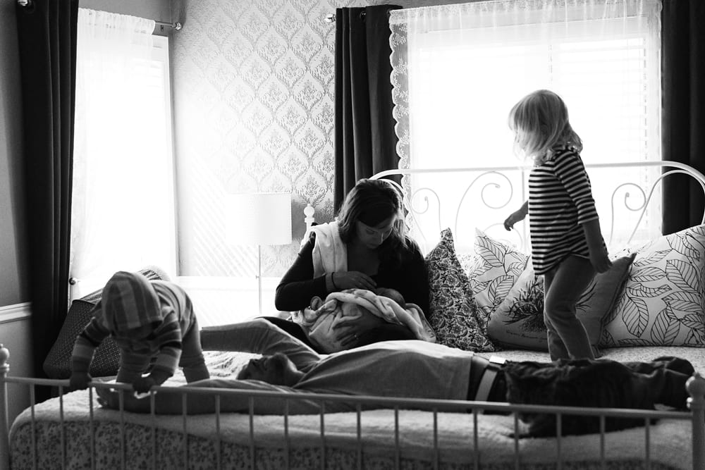 Cornwall family photographer - family playing on bed