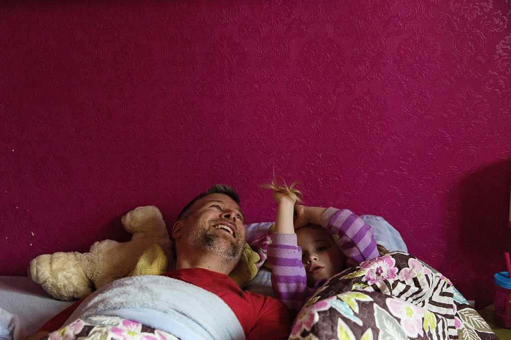 dad and daughter in bed with pink wall