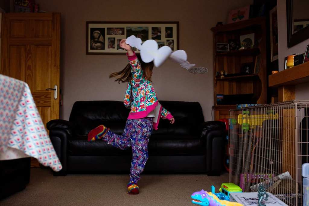 girl dancing with art project during London family photography session
