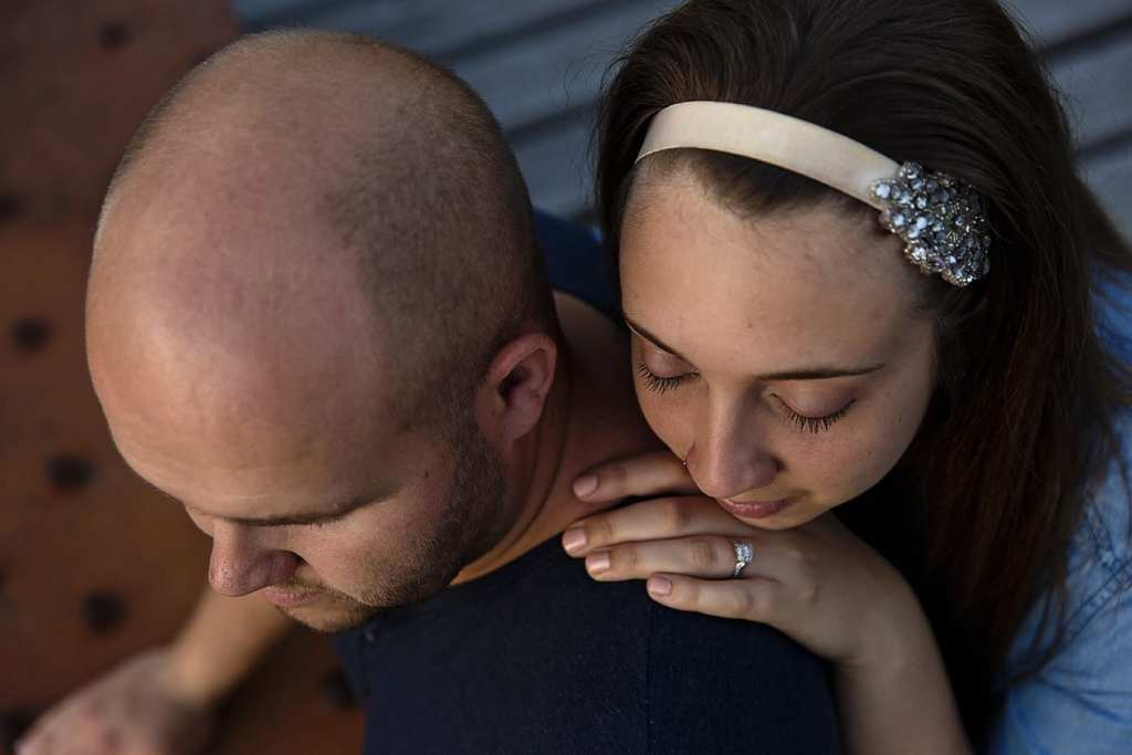Woman rests head on fiance's shoulder during St Raphael's engagement session