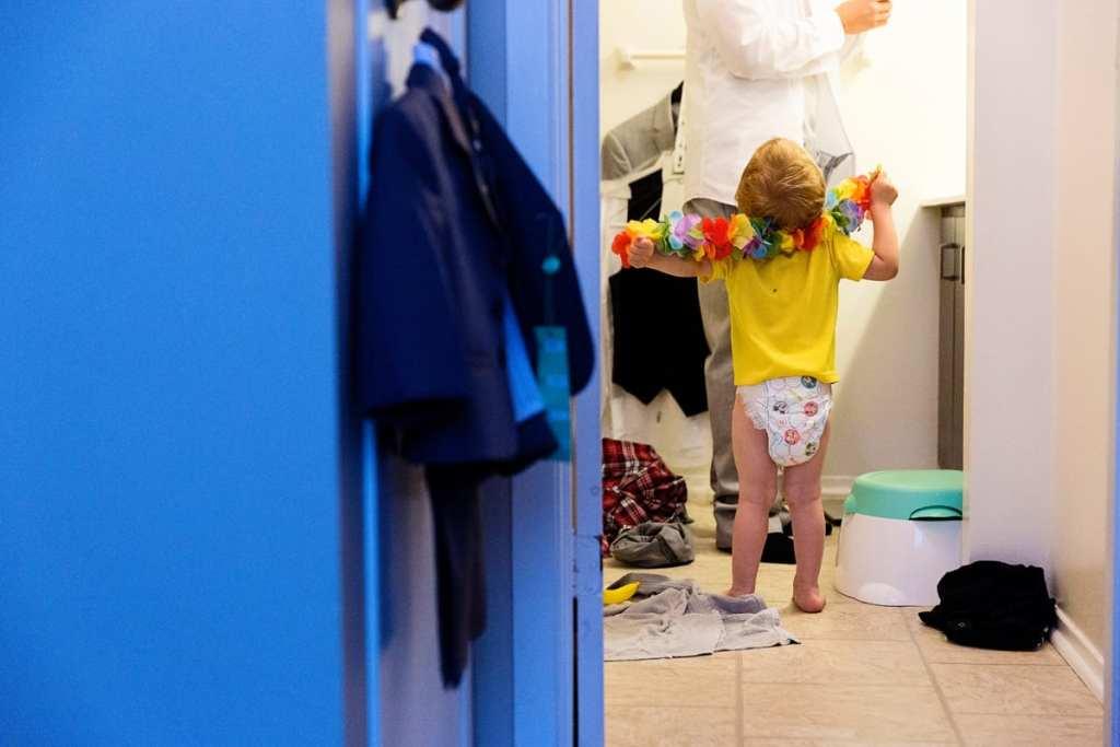 Ring bearer in bathroom trying to help groom prep for wedding