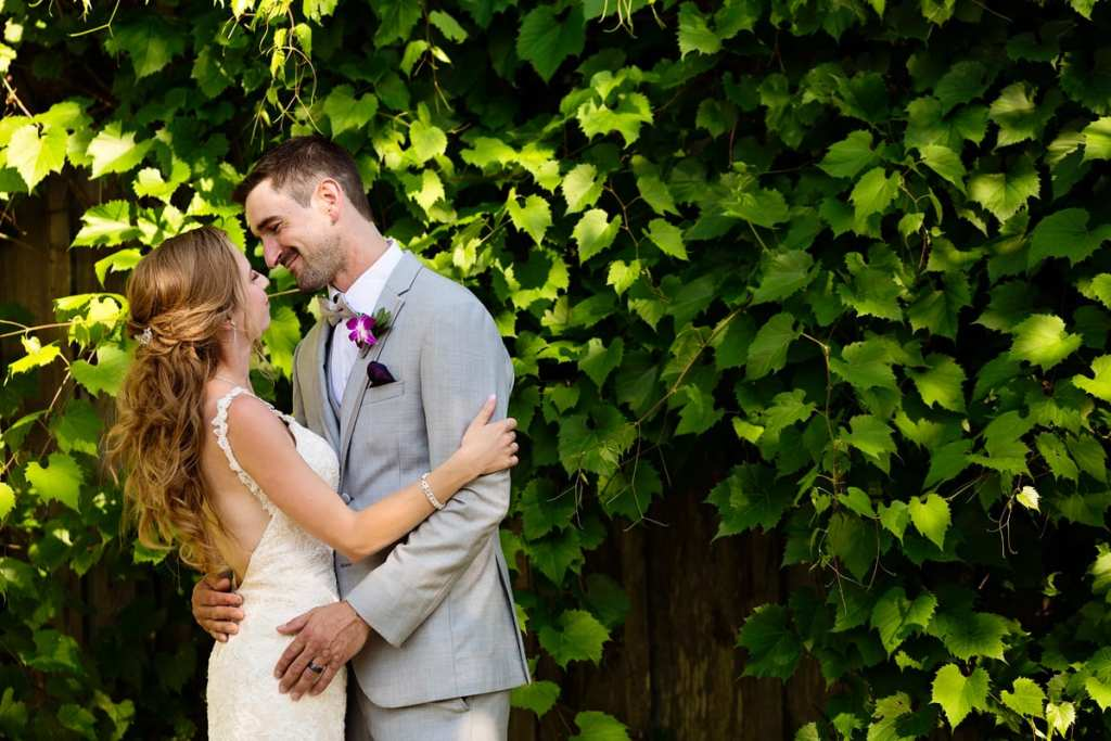 Bride in backless lace dress with groom in light grey suit