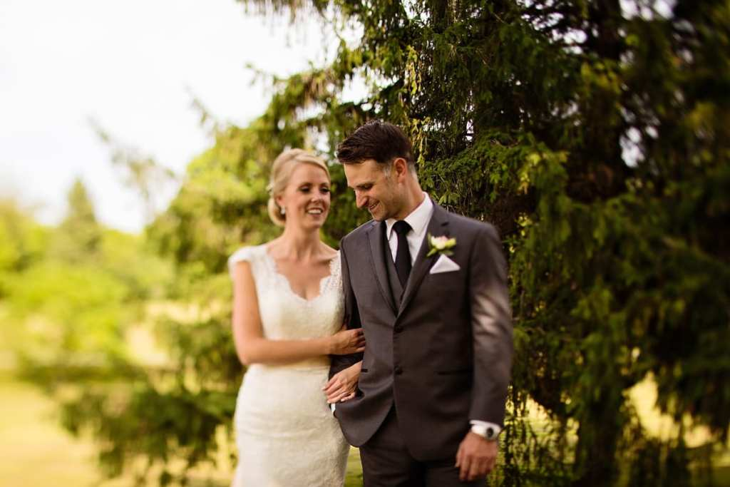 Bride in lace dress and groom in grey suit walk arm in arm