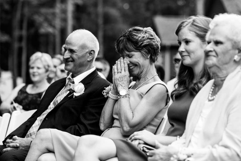 Groom's parents smiling during rural backyard wedding ceremony