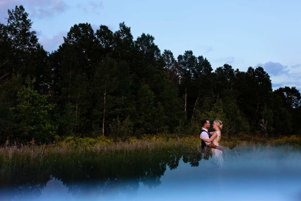 Bride and groom in evergreen tree stand with reflection
