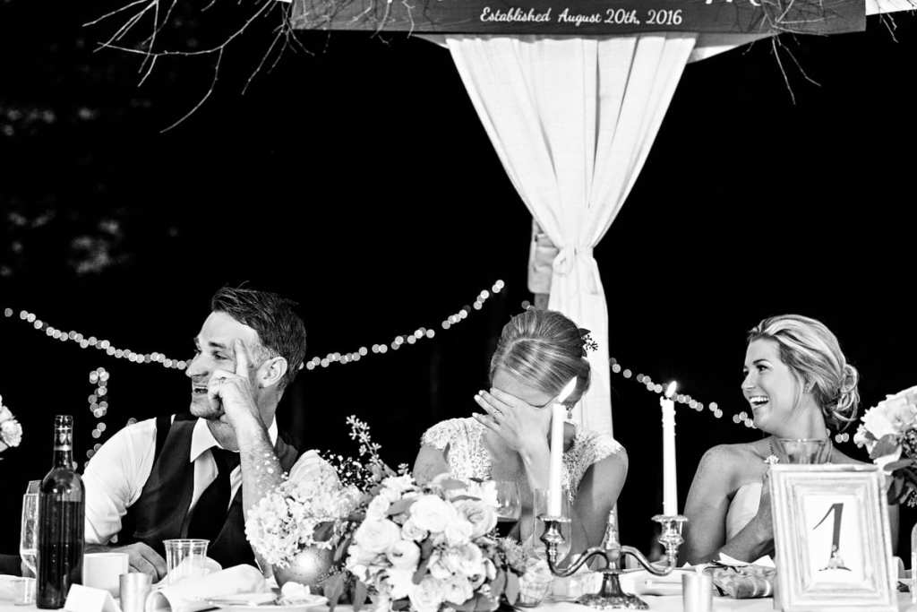 Bride and groom laughing with attendants at head table