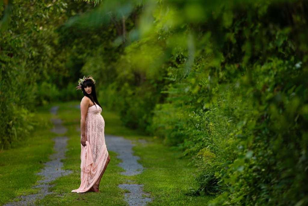 Bohemian woman in blush gown on lush green trail