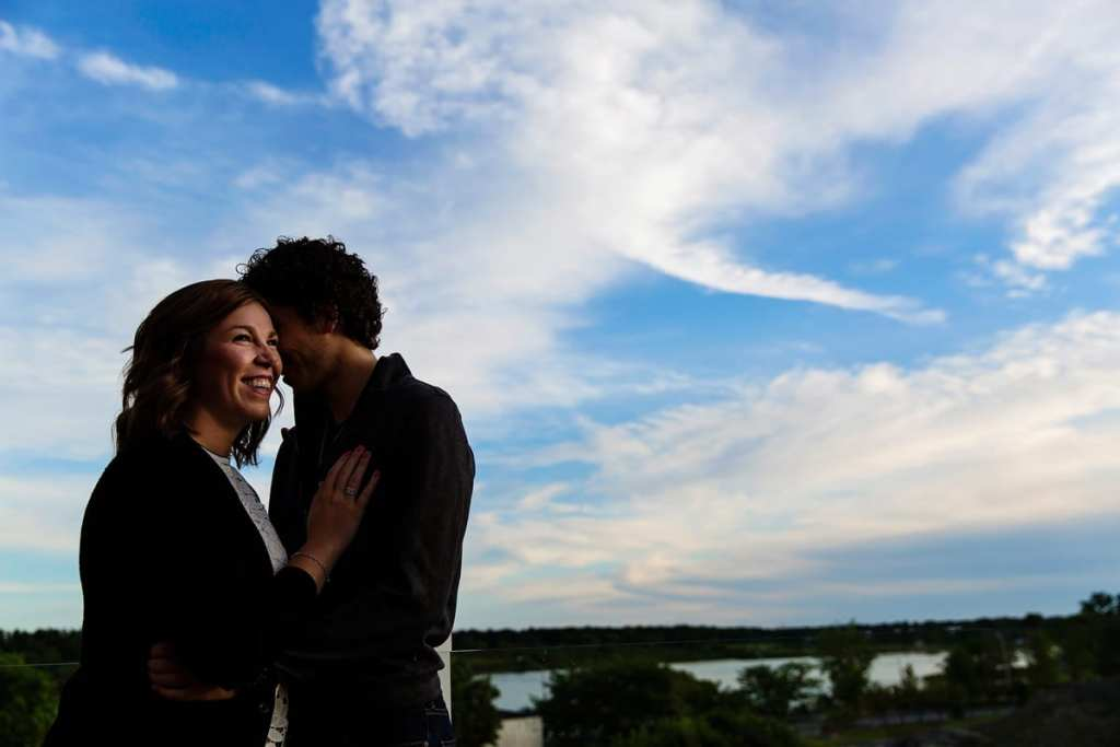 Beautiful couple in rooftop engagement session with river view