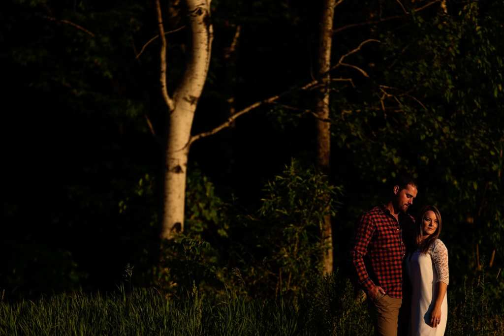 Man in plaid shirt and woman in white dress rural Cornwall engagement shoot