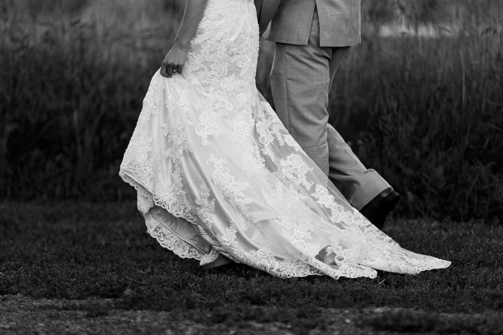 bride holds lace gown while walking past Strathmere field with husband
