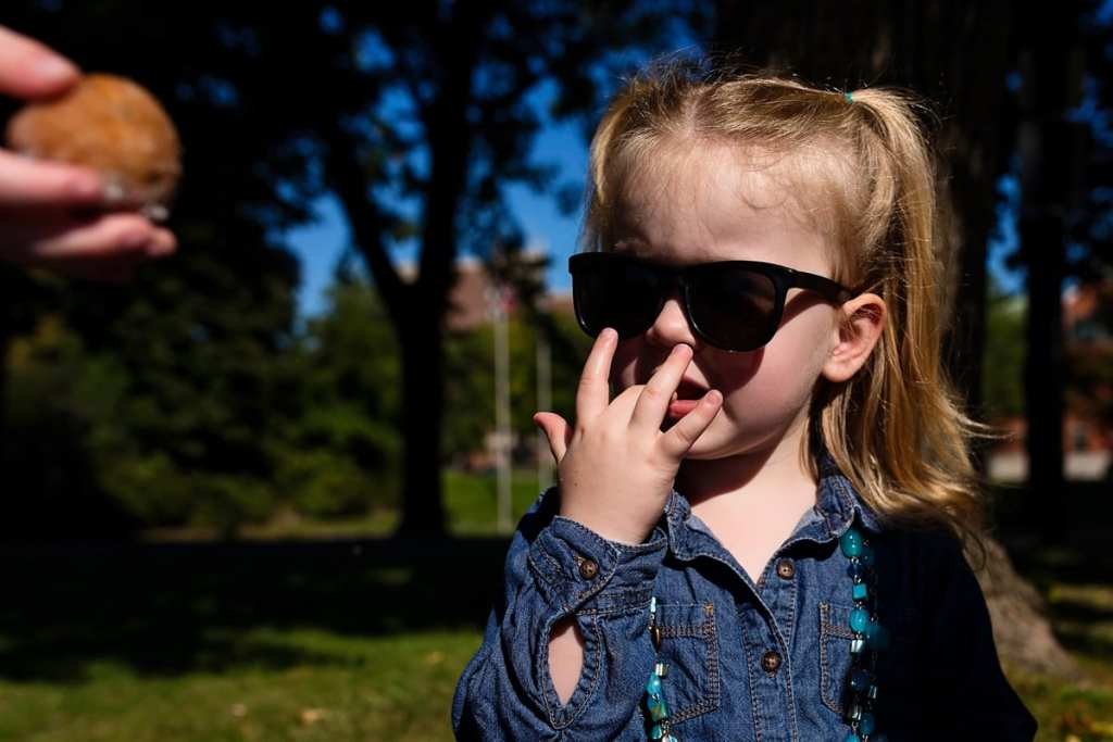 cool looking little girl wearing sunglasses licking her fingers during picnic in the park