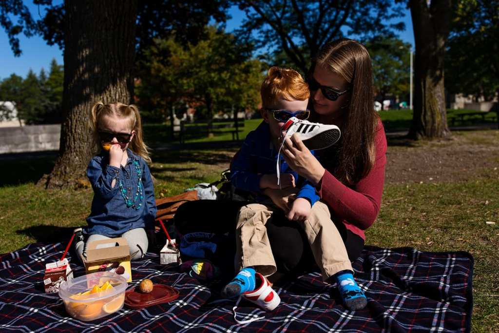 mom with son and daughter having picnic lunch in the park