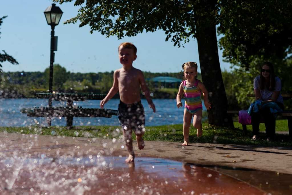 little boy and sister running and playing in Cornwall outdoor splash pad