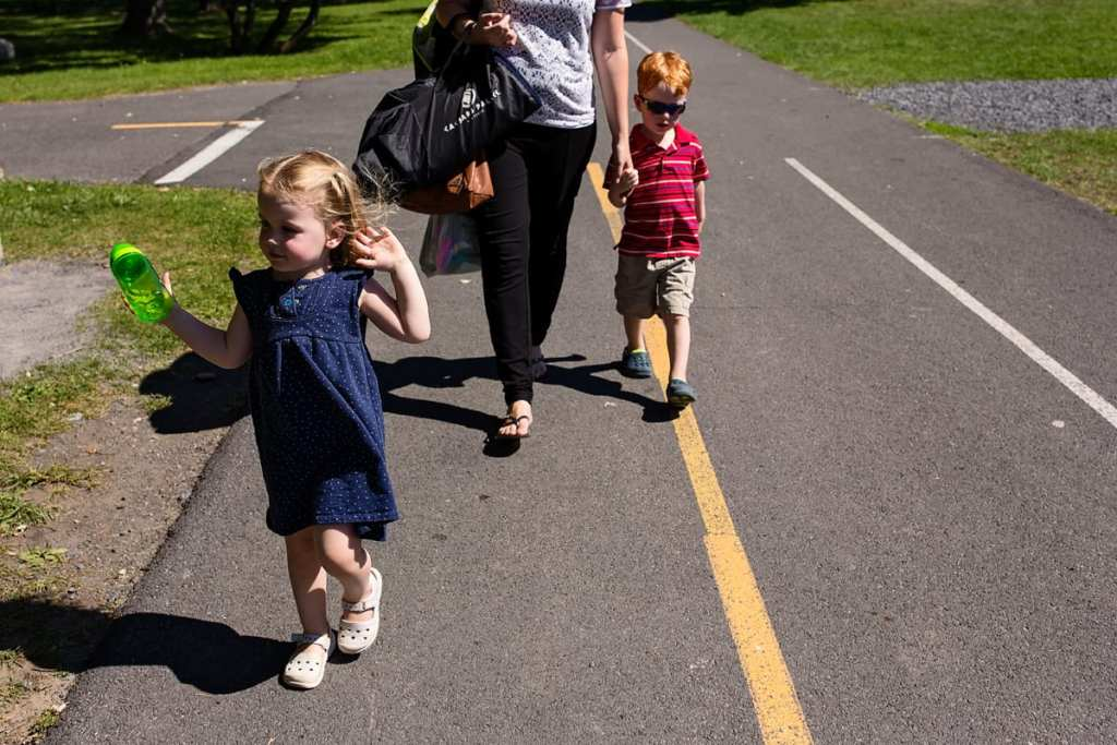 mom with son and daughter walking on path in summer sun
