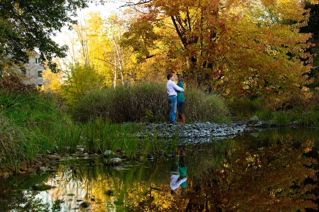 couple standing beside reflective pond in fall Martintown photo session