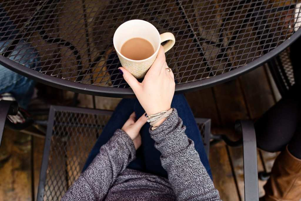 bracelet wearing young woman holding coffee at outdoor patio table