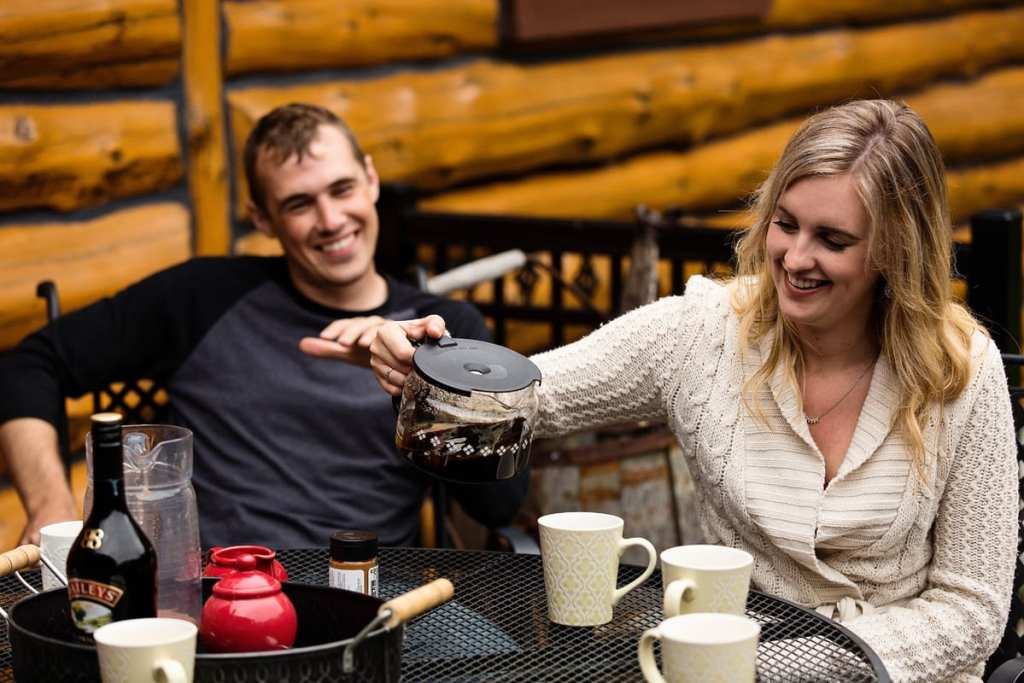 young woman pouring coffee while husband looks on smiling