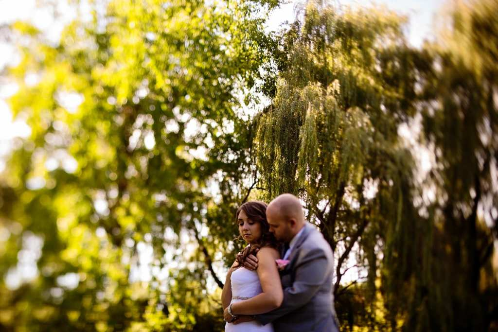 groom holds bride and nuzzles her neck in park