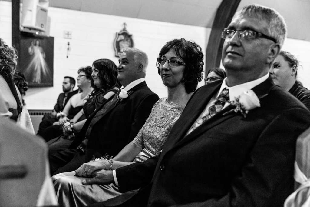 mother and father watch daughter get married during Cornwall evening wedding