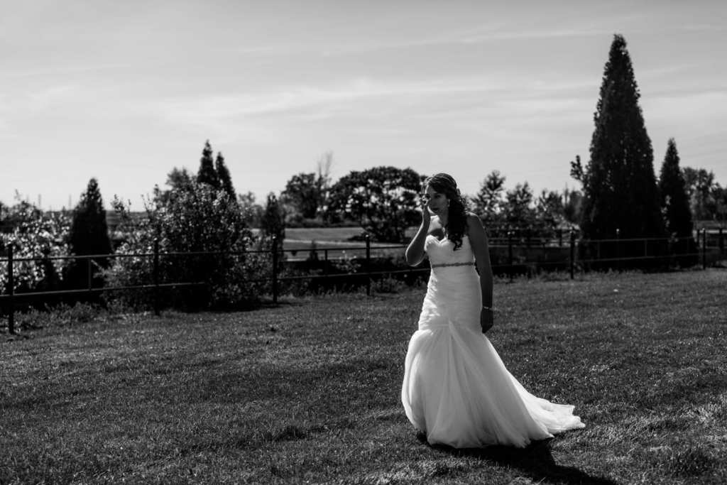 bride in fit and flare gown wipes tears while walking