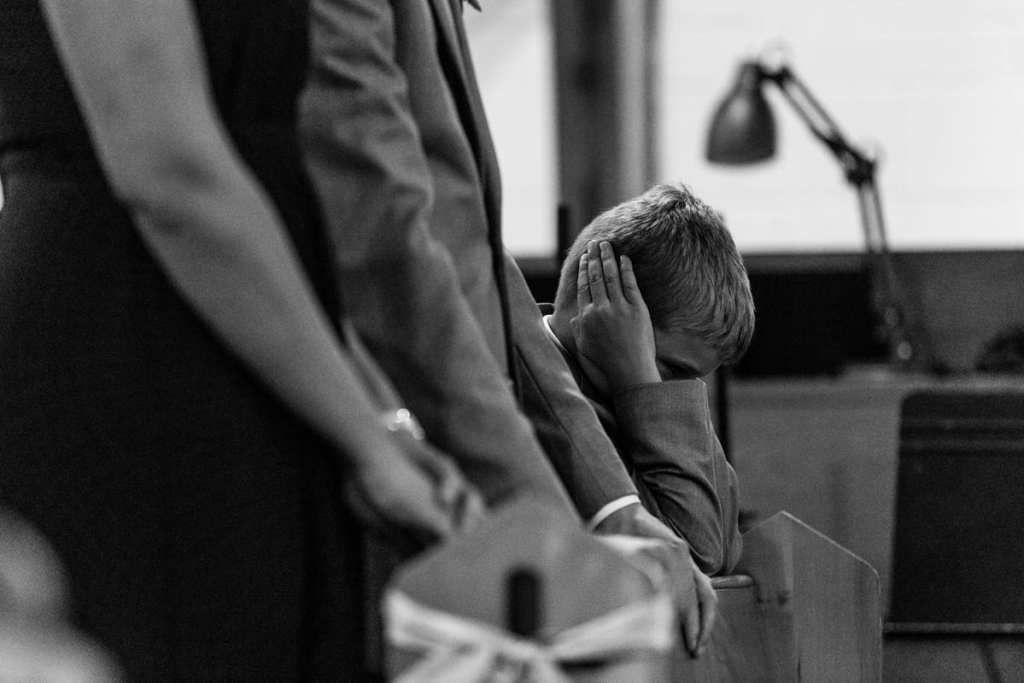 Boy blocks ears during Cornwall evening wedding