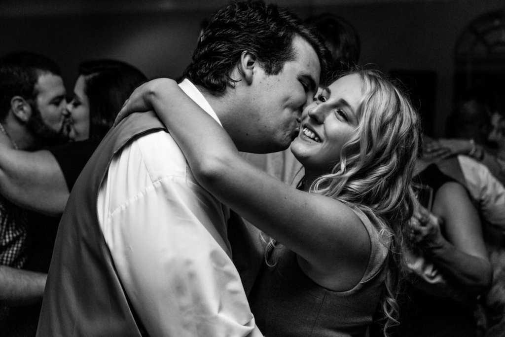 Man kisses woman's cheek during Cornwall evening wedding