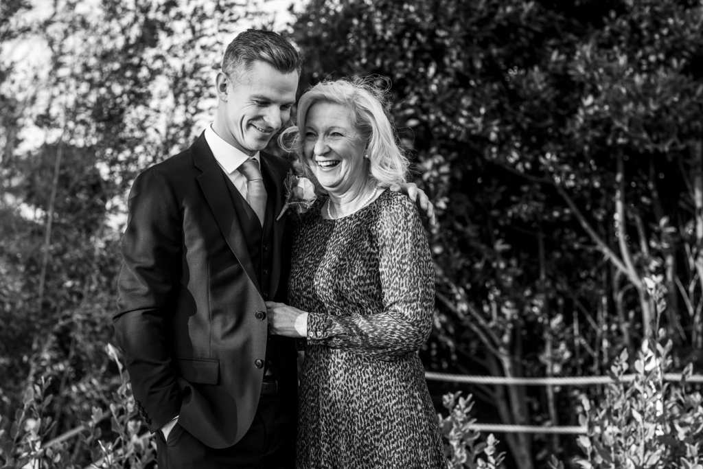groom laughs with mother during groom prep at Christchurch Habour Hotel & Spa
