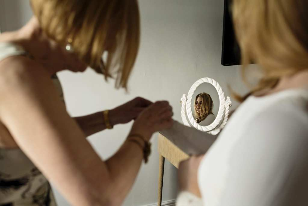 mother of the bride fastens sleeve buttons on bespoke bridal gown while bride's face shows in mirror during bridal prep at Christchurch Habour Hotel & Spa