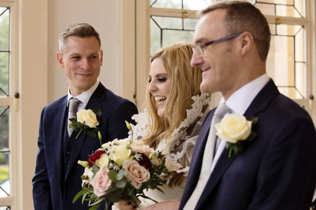 grooms looks at laughing bride when she reaches top of the aisle with father during chic New Forest wedding at Highcliffe Castle wedding ceremony