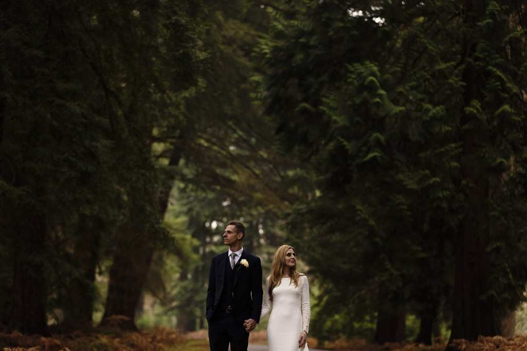 bride and groom hold hands while standing on road and looking up at trees on Rhinefield Ornamental Drive during chic New Forest wedding portraits