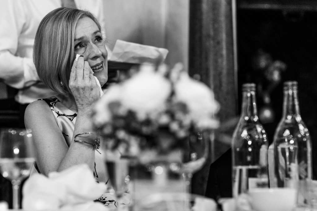 mother of the bride looks up and wipes tears away during wedding reception at Rhinefield House