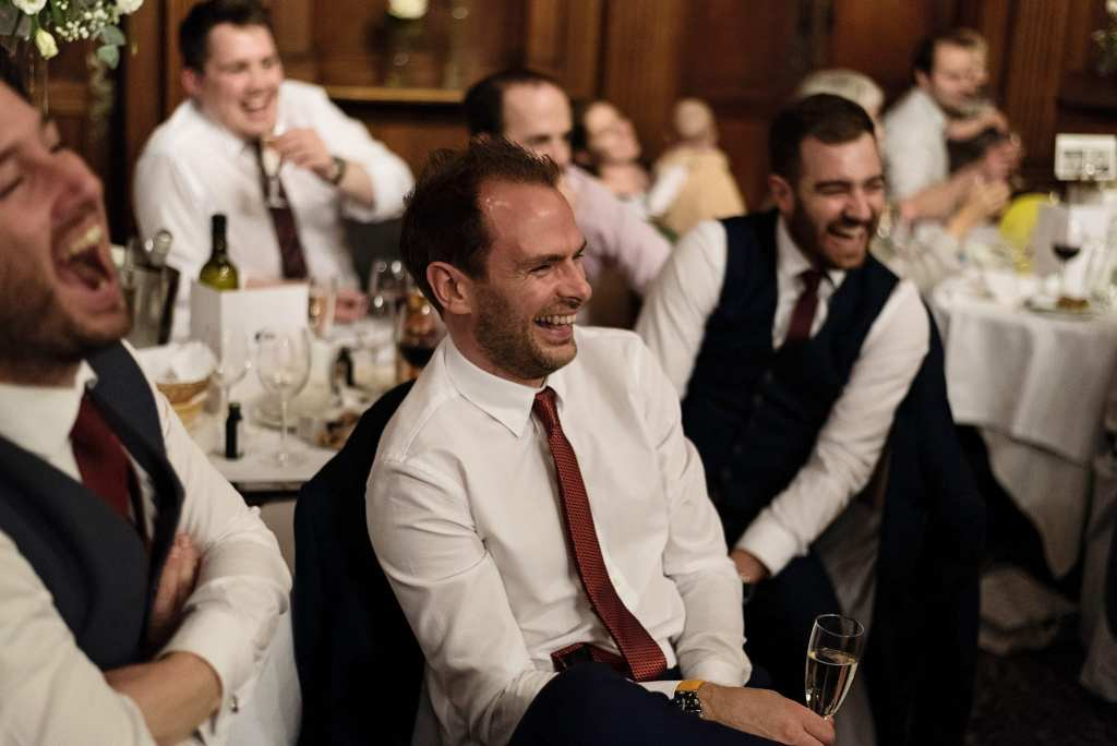 group of men laugh enthusiastically during wedding reception at Rhinefield House