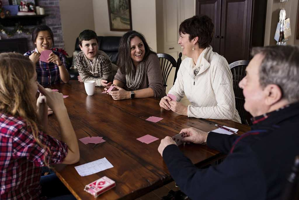 family sitting at kitchen table with red playing cards