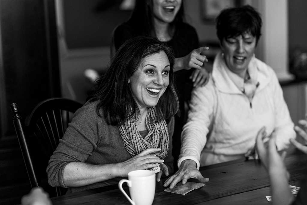 sisters laugh together at kitchen table while playing cards