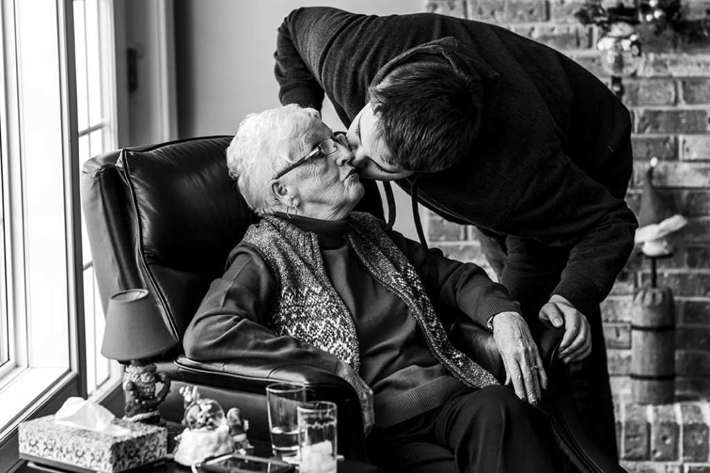 Grandson bends over grandmother's chair to kiss her on the cheek