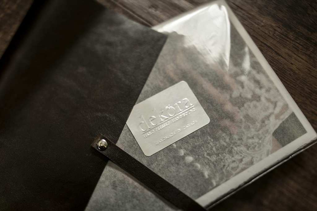 close up of Dekora Album Company packaging of modern Ontario wedding photos and dark leather photo satchel