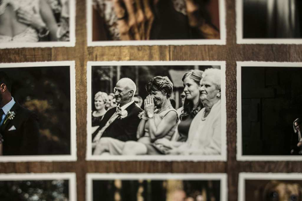 Hand torn matte printed modern wedding photos including mother of groom laughing while pressing hands to her face