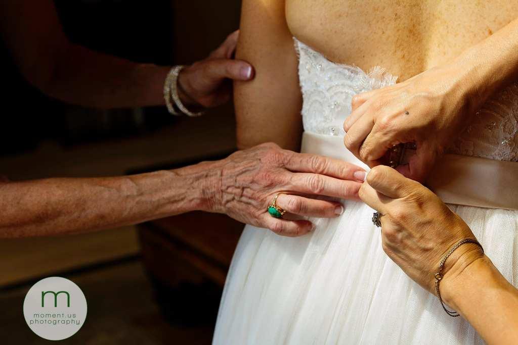 women's hands work on fastening bride's gown before Calabogie wedding