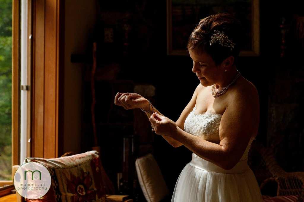bride fastens jewellery in soft window light before Calabogie wedding
