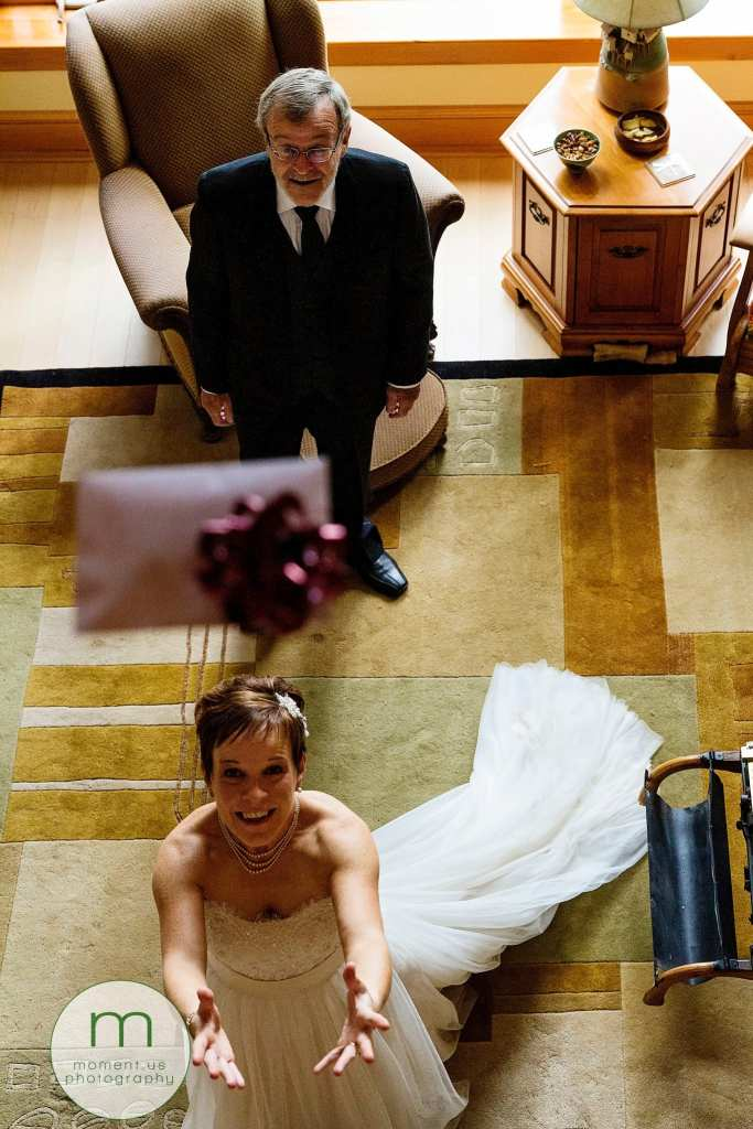 bride catches envelope being dropped from balcony while father looks on