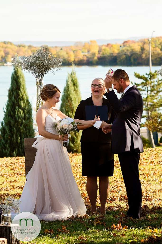 groom holds tissues in the air during wedding ceremony