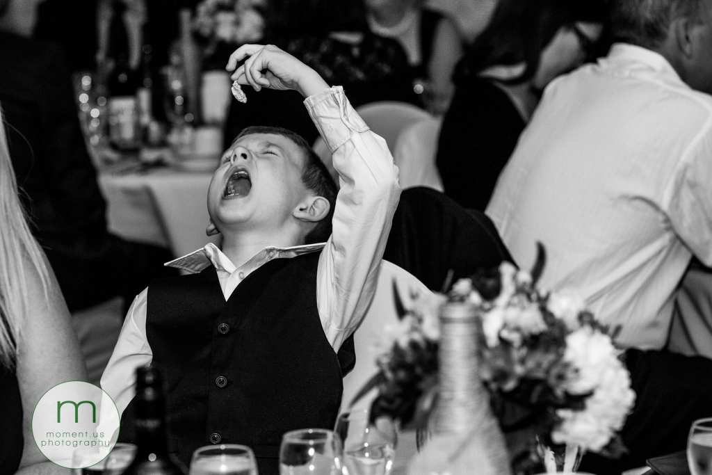 child dangles gum over his mouth during wedding reception