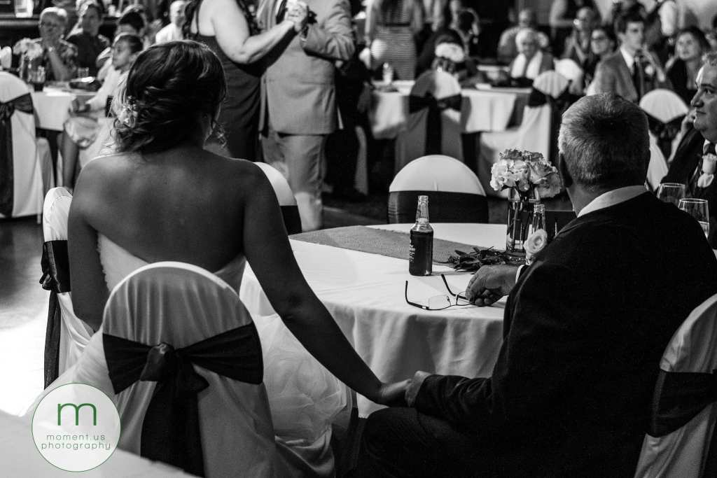 bride holds father's hand while groom dances with mother