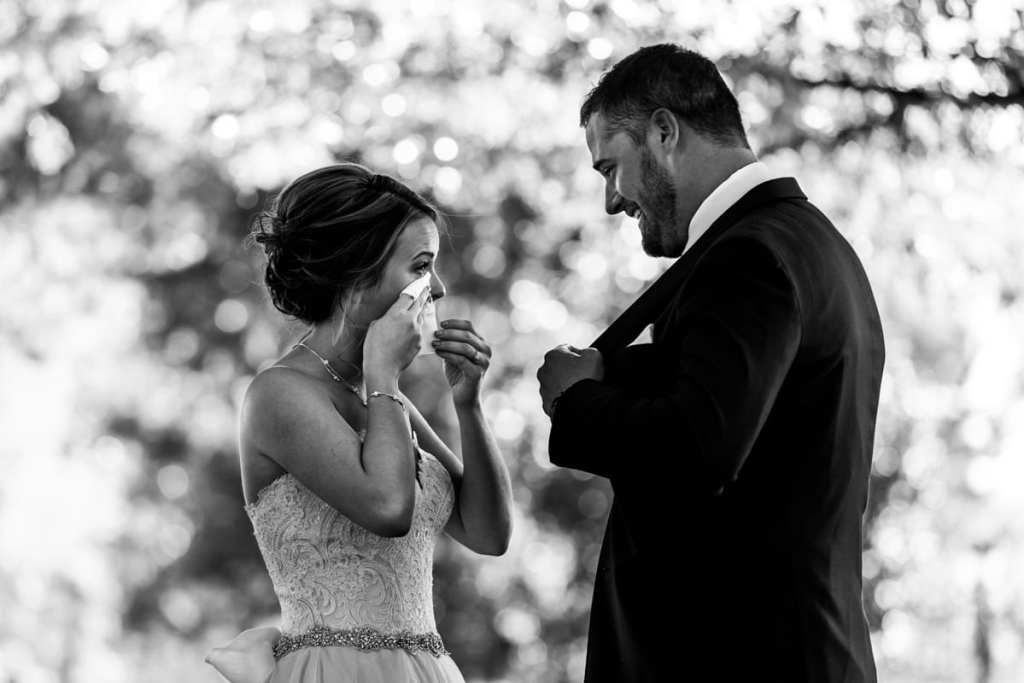 bride wipes tears during first look for Autumnal NAV Centre Cornwall Wedding