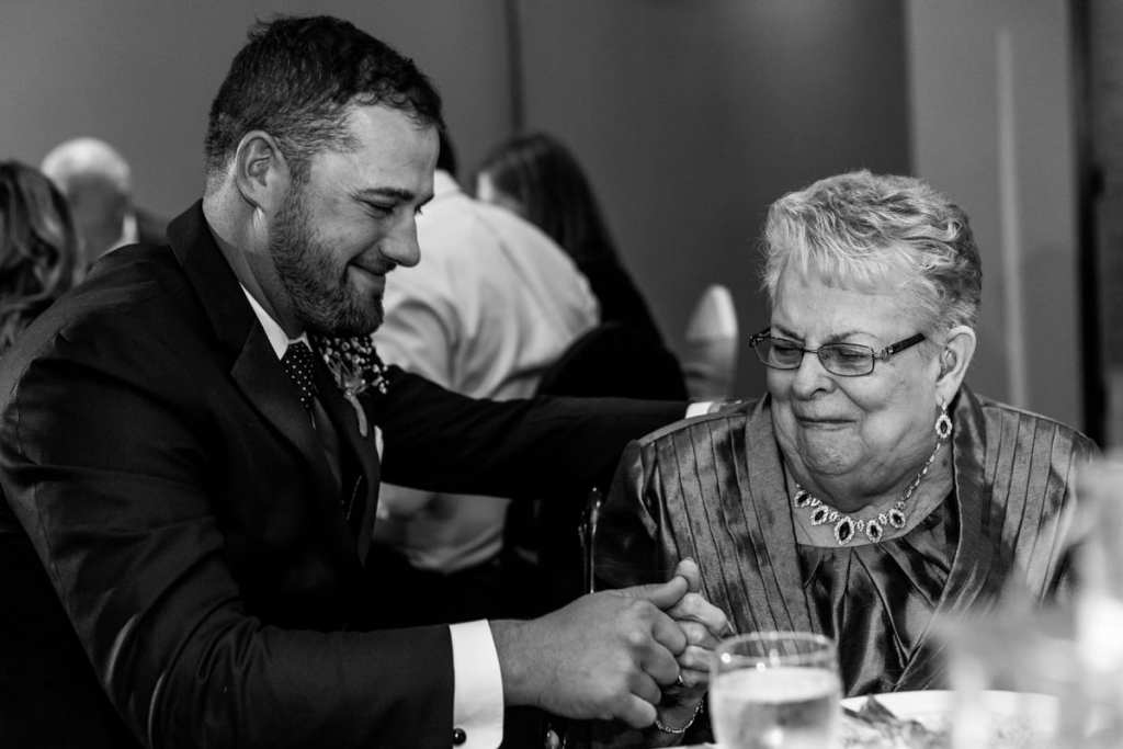 groom touching thumbs with grandmother during Autumnal NAV Centre Cornwall Wedding